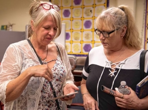 Cara Moser and Julie Foster look at photos and  talk about their daughters after a meeting of Harm Reduction Works in July at the Northampton Recovery Center. Both women lost their daughters to opioid overdoses and now are working to promote harm reduction practices.